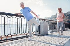 Satisfied unshaken man holding by the railing doing stretching exercises. Sport for everyone. Satisfied unshaken senior men spending time on fresh air holding Royalty Free Stock Photos