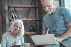 Satisfied unshaken man sitting and working with the laptop. Interesting information. Satisfied unshaken aged men sitting on the table near a women smiling and Stock Images