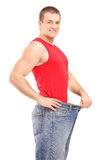 A satisfied weight loss man in a pair of old jeans. Isolated on white background royalty free stock photos