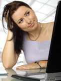 Satisfied woman behind a laptop. Smiling young female is sitting behind a laptop stock image