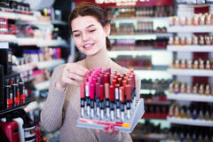 Satisfied woman customer deciding on make-up items in cosmetics. Satisfied woman customer deciding on make-up items on shelves in cosmetics shop Royalty Free Stock Image