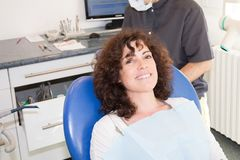 Satisfied woman dentist patient showing her perfect smile after treatment in clinic box with medical equipment. Background royalty free stock photography