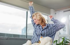 Satisfied woman full of energy at dawn. Lovely morning. Waist up portrait of drowsy girl relaxing on sofa. She is getting up and rising up her hands. Copy space Royalty Free Stock Photo