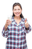 A satisfied woman with a glass of milk in pajamas on a white Stock Photography