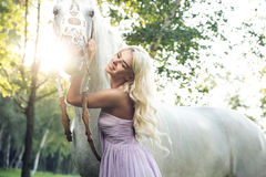 Satisfied woman hugging white horse stock images