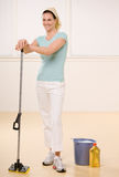 Satisfied woman posing with mop and floor cleaner. At home Royalty Free Stock Photography