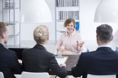 Satisfied woman during recruitment interview. Satisfied women telling recruiters about weaknesses and strengths during recruitment interview in the office Royalty Free Stock Images