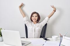 Satisfied woman relaxing with hands behind her head. Happy smiling employee after finish work, reading good news, break at work,. Girl doing simple exercise royalty free stock photos