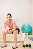 Satisfied woman resting on bench. In fitness studio Royalty Free Stock Images