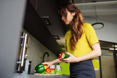 Satisfied woman standing in the kitchen picking vegetables