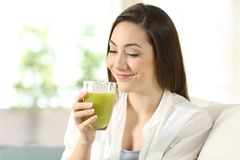 Woman tasting a good vegetable juice. Satisfied woman tasting a good vegetable juice sitting on a couch in the living room at home Stock Photography
