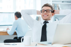 Satisfied with the work done. Cheerful businessman in formalwear holding head in hands while sitting at his desk in the office Stock Photography