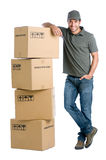 Satisfied worker with boxes. Satisfied and proud delivery man leaning on a stack of boxes isolated on white background Stock Photography