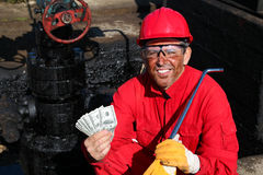 Satisfied Worker Holding Money at Oil Field. Smiling oil worker in red overalls and hardhat holding US dollar bills in his hands. Selective focus Stock Photos