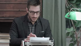 Satisfied writer finished typing his book and taking his glasses off stock video