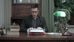 Satisfied writer in glasses finishing typing another chapter of his book stock footage