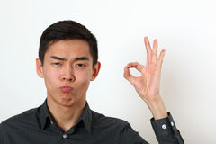 Satisfied young Asian man giving the okay sign and looking at ca Stock Photos