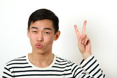 Satisfied young Asian man giving the victory sign and looking at Stock Images