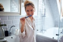 Free Satisfied Young Caucasian Blonde Female Thinking With Smile While Brushing Her Teeth In The Bathroom Stock Photos - 216316573