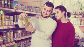 Satisfied young couple choosing purchasing canned food for week. Satisfied young couple choosing ordinary family purchasing canned food for week at supermarket Stock Image