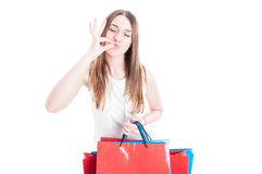 Satisfied young customer doing shopping in her leisure. And doing sign for perfection on white background royalty free stock images