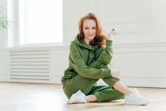 Satisfied young female with red hair, being in good body shape, does yoga stretching exercises, strengthens muscles, dressed in royalty free stock photography