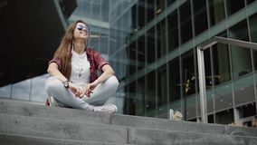 Portrait of beautiful woman in casual clothes sitting on stony stairs on the background of modern glassy building stock video