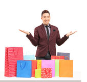 Satisfied young man posing with plenty of shopping bags Stock Photo