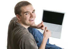 Satisfied Young Man Using a Laptop Royalty Free Stock Photos