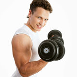 Satisfied young strength man lifting dumbbell Royalty Free Stock Image