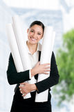Satisfied young woman architect. With her plans looking at camera outdoor in the city royalty free stock images