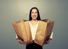 Satisfied young woman with paper bags. Over dark background stock image