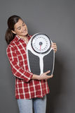 Satisfied young woman standing with  her weight scale in hands Royalty Free Stock Photo
