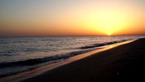 Satisfying lugna långsamma vågor som kraschar på sand, sätter på land kustlinjen för havskusten i orange solnedgångseascape för m lager videofilmer