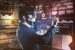 Cheerful specialist smiling while wearing virtual reality device. Satisfying view. Positive young professional programmer looking pleased while experiencing new Royalty Free Stock Images