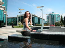 Satisfying work. Girl working on a laptop outdoors, on the fountain, business background. Relaxed job. Easy going Royalty Free Stock Image