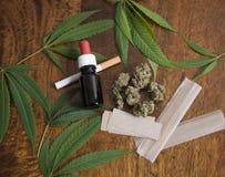 Sativa ogräsblad för cannabis och blommaknoppar på träbakgrund med THC-olja, cigarett och rökalegitimationshandlingar Arkivfoto