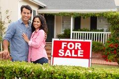 satnding与在房子之外的一个符号的西班牙夫妇 免版税库存图片