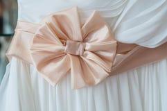 Satängpilbåge på en vit bröllopsklänning Royaltyfri Bild