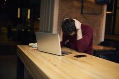 Satressed et homme d'affaires inquiété utilisant l'ordinateur portable et libèrent la connexion sans fil à l'Internet pendant le  Image stock