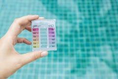 Sats för prov för provning för vatten för flickahand hållande mini- över blå simbassängvattenbakgrund royaltyfri bild