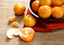 Satsuma oranges in a wooden bowl. Presented on wooden bamboo mat Royalty Free Stock Photos