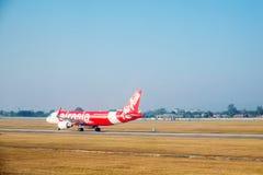 SATTAHIP, THAILAND - 21. Dezember - das Passagierflugzeug Air- Asiafluglinie an U-Tapaoflughafen mit getrocknetem Gras rieb in Th Lizenzfreie Stockfotos