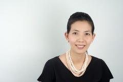 Satte asiatiska kvinnor för stående de pärlemorfärg smyckena i den svarta klänningen för PA Royaltyfria Bilder