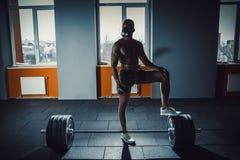 Satte den idrotts- mannen för afrikanska amerikanen i sportmaskering hans fot på skivstången som väntar och förbereder sig, innan Arkivbilder
