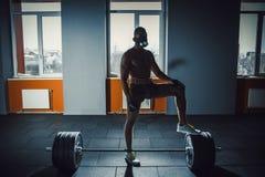 Satte den idrotts- mannen för afrikanska amerikanen i sportmaskering hans fot på skivstången som väntar och förbereder sig, innan Royaltyfri Bild