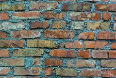 A saturated contrast photograph of the old, weather-destroyed wall of red brick casually laid on a large layer of cement. Best for background royalty free stock image