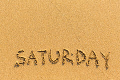 Saturday - inscription by hand on a light-golden beach. Sand stock photography