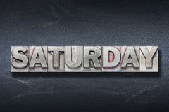 Saturday word den. Saturday word made from metallic letterpress on dark jeans background stock photos
