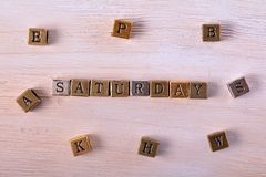 Saturday word metal block. Saturday word gold and silver metal block on white wood with letter blocks around stock image
